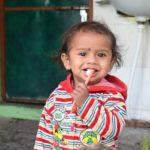 Little girl brushing teeth outside
