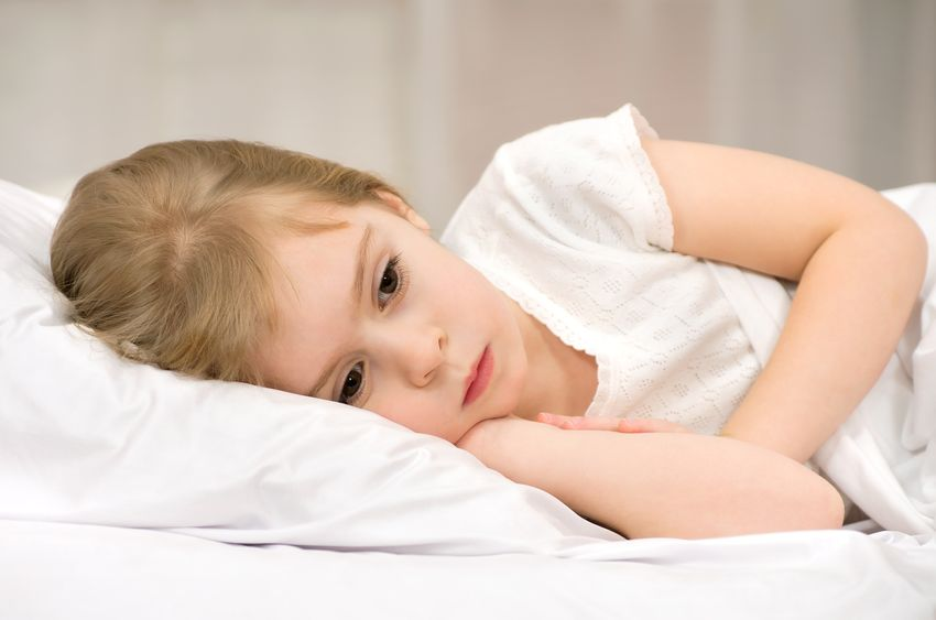 Child lying in bed suffering from tooth pain
