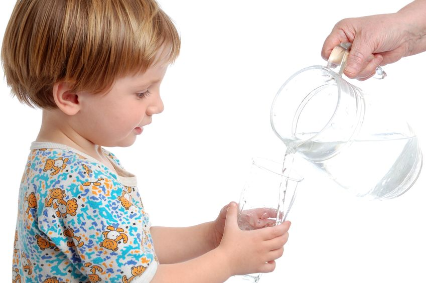 Child drinking tap water poured from a pitcher